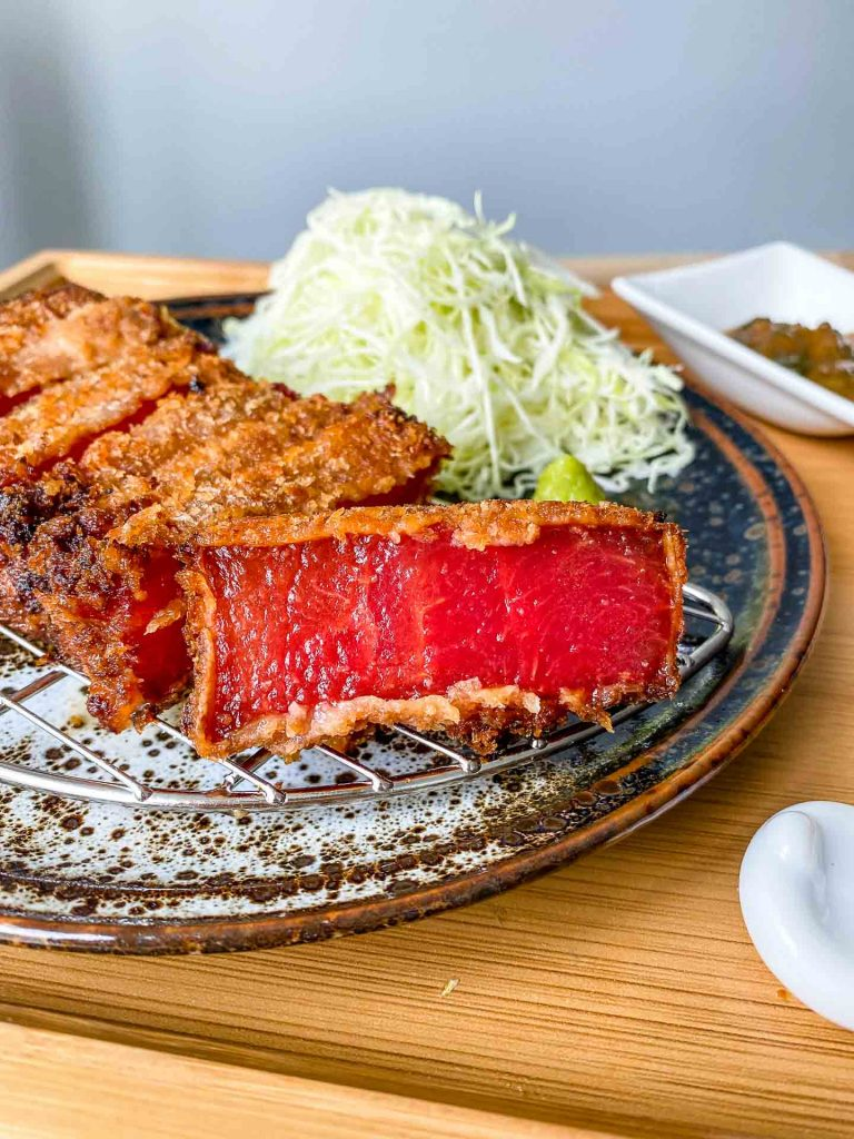 watermelon katsu on a wire rack with cabbage behind it