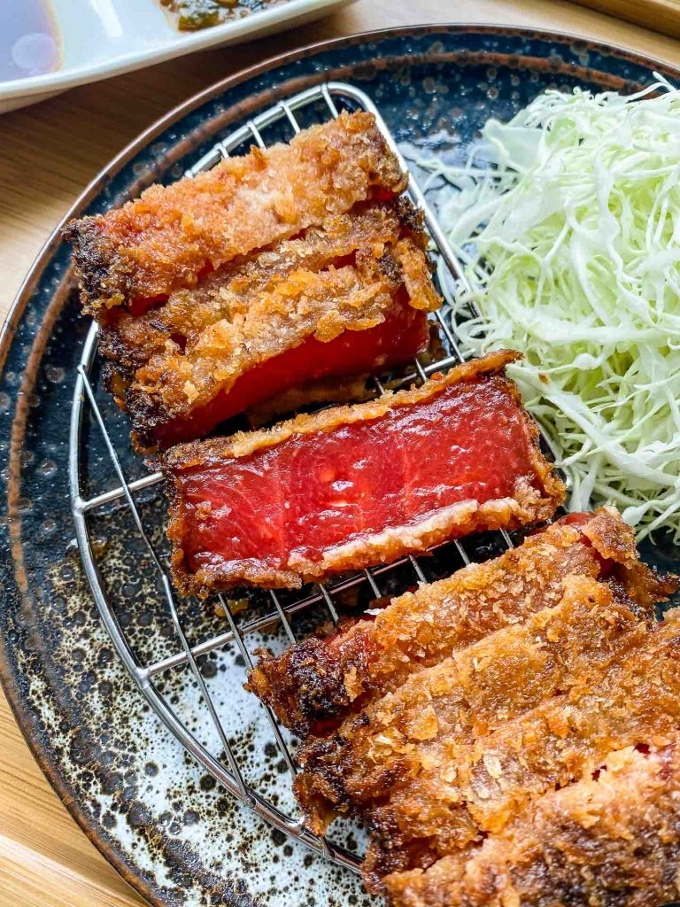 watermelon katsu on a wire rack with one piece showing the inside