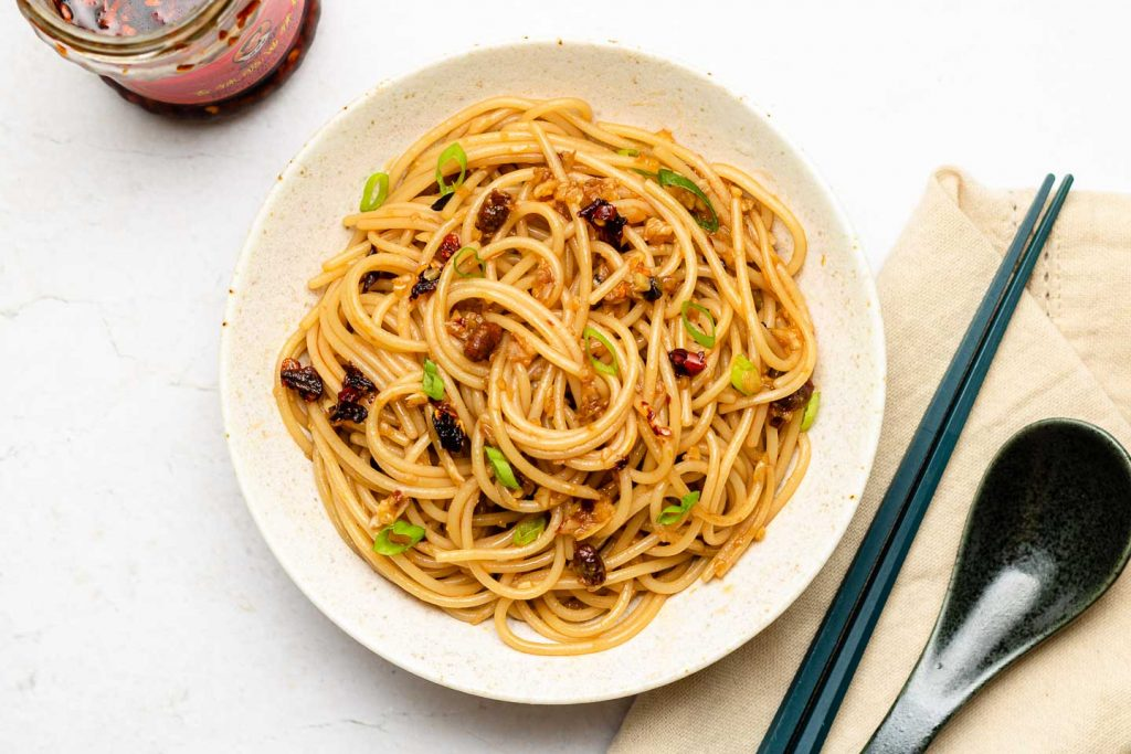 garlic noodles in a white plate with chopsticks and spoon beside it