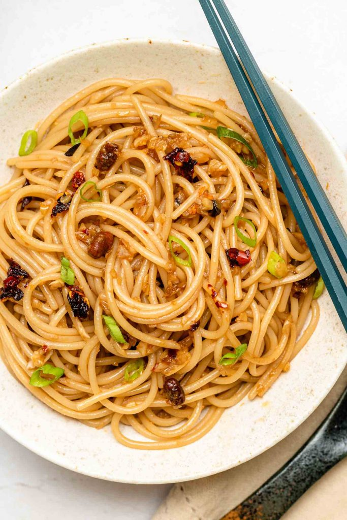 garlic noodles in a shallow white bowl with scallions and chili crisp oil