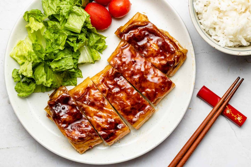 yuba teriyaki tofu chicken on a white plate with lettuce and tomatoes
