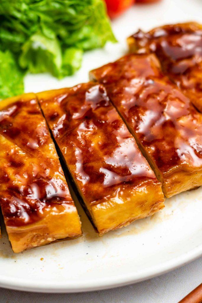 vegan teriyaki tofu on a white plate sliced into bite sized pieces