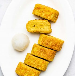 rolled omelette on a white plate with grated daikon beside it